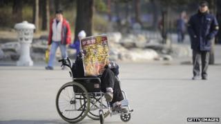 An elderly woman in a wheelchair reads on her own in a park in Beijing