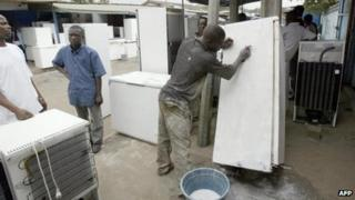Man cleaning a fridge in Ivory Coast (file photo)