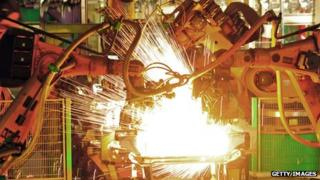 Car chassis being welded by robots