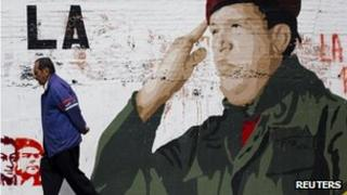 A man walks past a mural depicting President Hugo Chavez