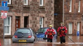 Firemen walk through floodwater on the High Street in Stonehaven