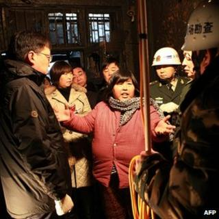 Woman identified as Yuan Lihai talks to officials at scene of fire. 4 Jan 13
