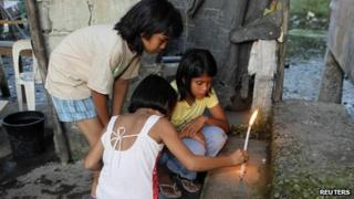 Relatives of shooting victim Micaella Andrea Caimol light candles at the steps of her house in the Cavite province, 4 January