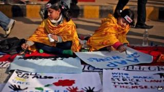 Children paint messages of support for the victim in Delhi, 5 January
