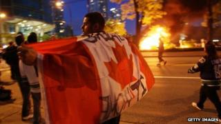 A rioter walks through Vancouver with a Canadian flag 15 June 2011