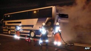 Firefighters spray a burning Belgian coach near Goeschenen, Switzerland, 8 January
