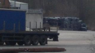Container lorry in front of bales of waste