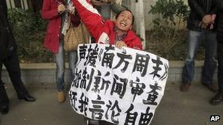 """A man holds a banner saying """"Support Southern Weekly, boycott news censorship and return my freedom of speech"""" outside the newspaper""""s headquarters in Guangzhou on 8 January 2013"""