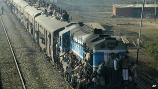 Passengers sit on top of a crowded Indian train
