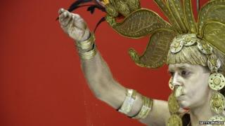 A man dressed as the mythic figure of El Dorado sprinkles gold dust