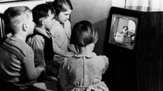 Children gather round a black and white television