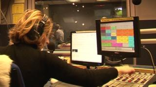 A radio presenter at her console