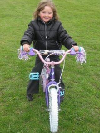 April Jones on her pink and purple bicycle