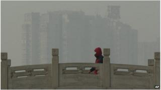 A man wearing a mask walks over a bridge in smoggy Beijing (14 Jan 2013)