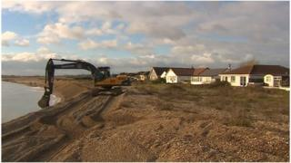 Digger adding gravel to beach at Pagham