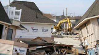 A crane is seen at a distance as two damaged homes rest off their foundation in Seaside Heights, NJ 8 January 2013