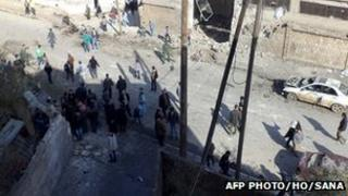 A Syrian State news agency-provided photo of officials inspecting bomb damage in Idlib