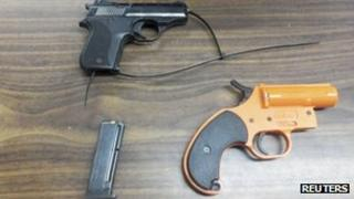 A handgun, ammunition clip and flare gun found in the bag of a sevem-year-old boy, police handout 18 January 2013
