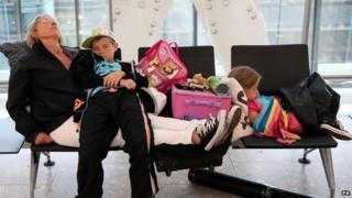 Family sleeping at Heathrow Airport