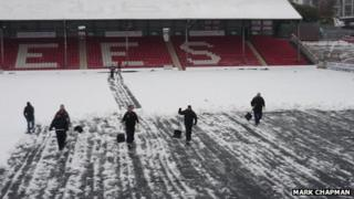 Fans clearing snow from the pitch