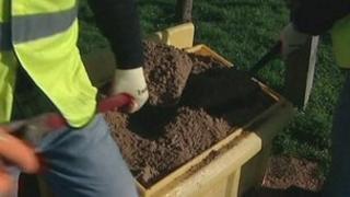 Grit salt being shovelled from a grit bin