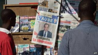 Men look at the front pages of newspapers on January 21, 2013 in a street of Bamako.