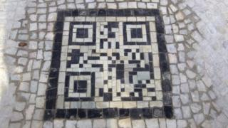 A mosaic QR code built into the pavement in Brazil.