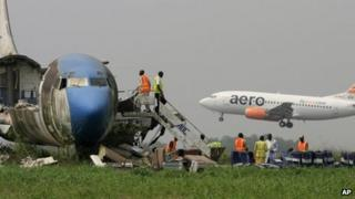 A passenger plane lands as workers dismantle an abandoned aircraft at Murtala Muhammed International Airport in Lagos, Nigeria, on 31 January 2013