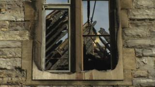 A view through a burned window at the derelict Butleigh Hospital site