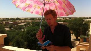 Thomas Fessy reading under umbrella
