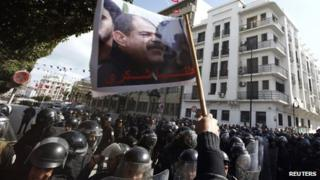 Tunisian protesters shout slogans during a demonstration after the death of opposition leader Chokri Belaid (pictured on flag), outside the Interior ministry in Tunis on Wednesday 6 February 2013