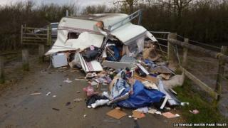 A caravan, filled with household waste, is dumped at Waterhay car park, part of Cotswold Water Park