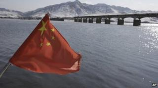 A Chinese flag is hoisted near the Hekou Bridge (R) linking China and North Korea, in Hekou, China, 7 February 2013