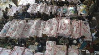 Pakistani Shiite Muslims gather around the coffins of bomb attack victims as they demonstrate in Quetta on February 18