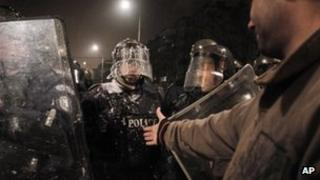 Bulgarian protester against high electricity prices confronts riot police in Sofia