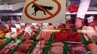 "A butcher works behind a ""no horsemeat"" sign at Bates Butchers in Market Harborough, central England"