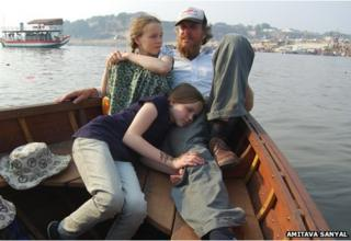 Andrew Turner takes a ride in his boat, Karuna, on the Yamuna with his daughters Gemma and Elle