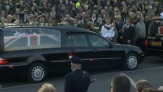 Two hearses drive past a large crowd in Carterton