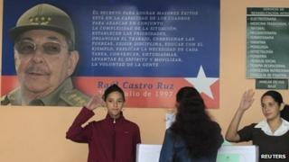 Schoolgirls salute as a woman casts her ballot to elect a Communist Party-selected slate of 612 deputies to the National Assembly (3 February 2013)