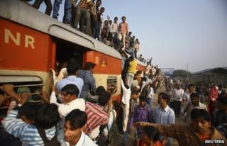 Commuters struggle to board a train at Noli railway station in Uttar Pradesh November 10, 2012.