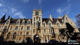 A woman cycles past Balliol College in Oxford