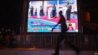 A man walks past a large screen in Central Nairobi broadcasting the last televised debate for the 2013 Kenya elections on 25 February 2013