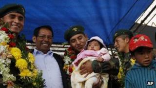 Bolivian soldier Alex Choque (c) holds his son as fellow soldier Jose Luis Fernandez (l) and Augusto Cardenas (r) look on