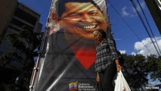 A woman walking past a poster of Hugo Chavez