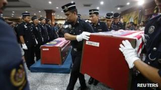 Malaysian police carry a colleague's coffin