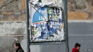 People walk next to ripped electoral posters in Rome. Photo: February 2013