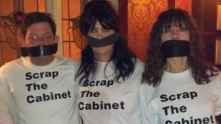 Mark Sharp, Patsy Link and Sheena Walker wearing 'Scrap the Cabinet' T-shirts