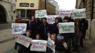 People standing in front of an open top bus waving placards reading: save our buses