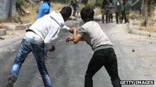 Palestinian youths throw stones towards Israeli soldiers near Hebron (file photo)