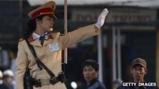A Vietnamese police woman directs traffic in Hanoi